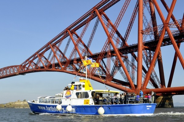 Tour boat painted blueand white alongside Forth Bridge
