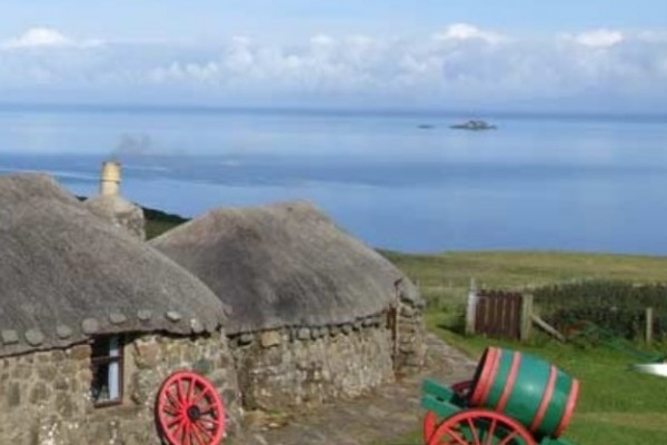 Ancient cottage with thatch roof overlooking the sea on the Isle of Skye